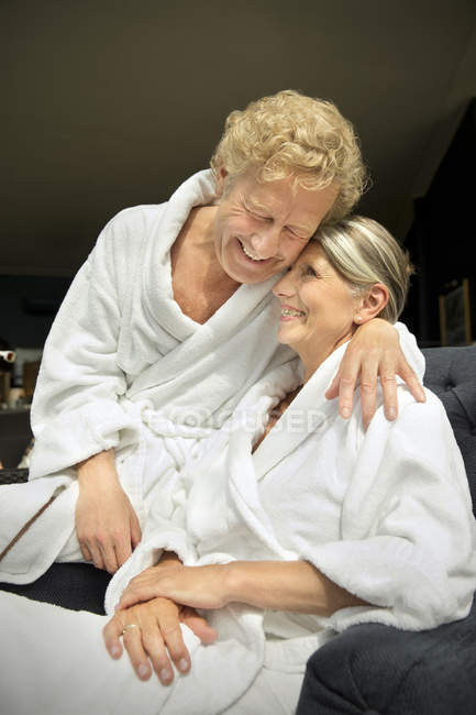 Happy senior couple in bathrobes hugging in armchair — Stock Photo