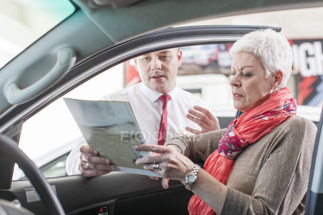 Car dealer showing new car to woman in showroom — Stock Photo