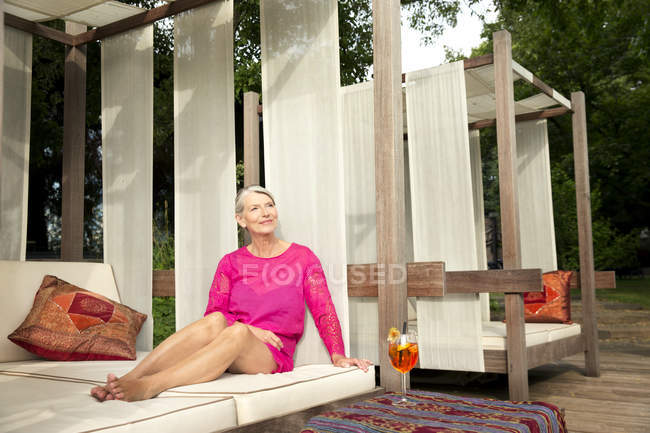 Smiling senior woman sitting on lounge outdoors with cocktail — Stock Photo