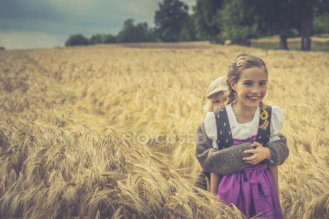 Duas crianças de pé em um campo de grãos — Fotografia de Stock