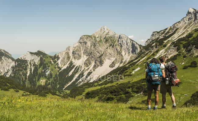 Austria, Tirolo, Tannheimer Tal, giovane coppia in piedi sul prato alpino — Foto stock