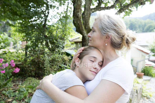 Mother and daughter hugging in garden — Stock Photo