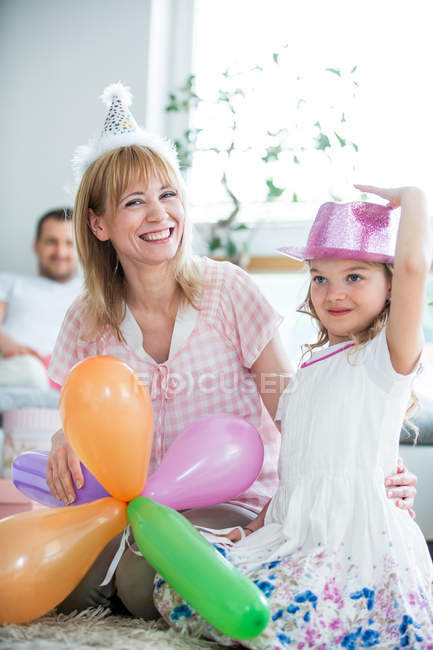 Семья празднует с воздушными шарами и шляпами для вечеринок дома — стоковое фото