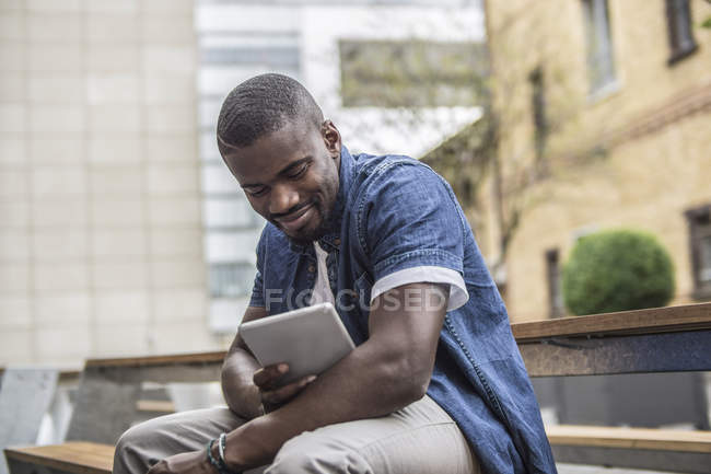 Man sitting on bench with digital tablet — Stock Photo