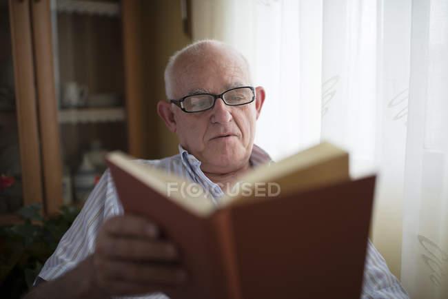 Senior man reading a book at home — Stock Photo