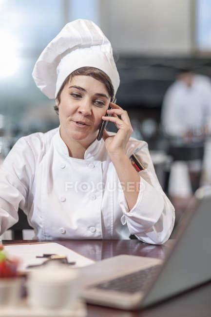 Chef del ristorante seduto a tavola con il cellulare — Foto stock