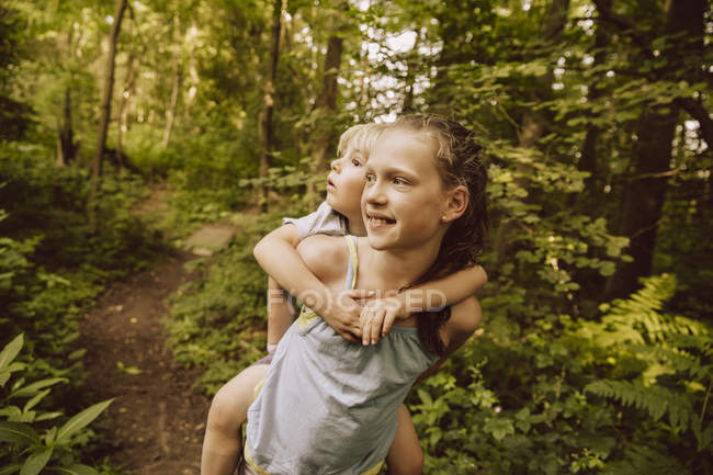 Mädchen trägt kleinen Jungen huckepack durch den Wald — Stockfoto