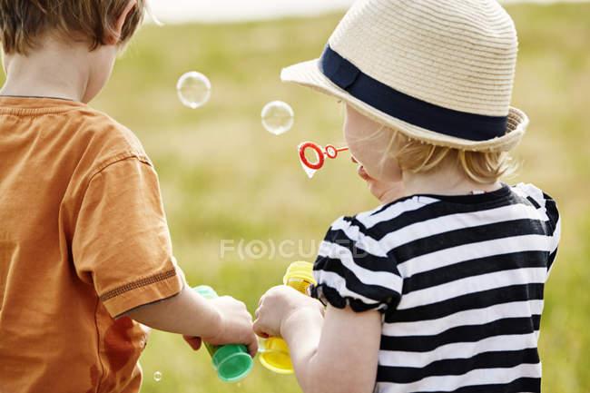 Вид сзади маленьких детей, выдувания мыльных пузырей — стоковое фото