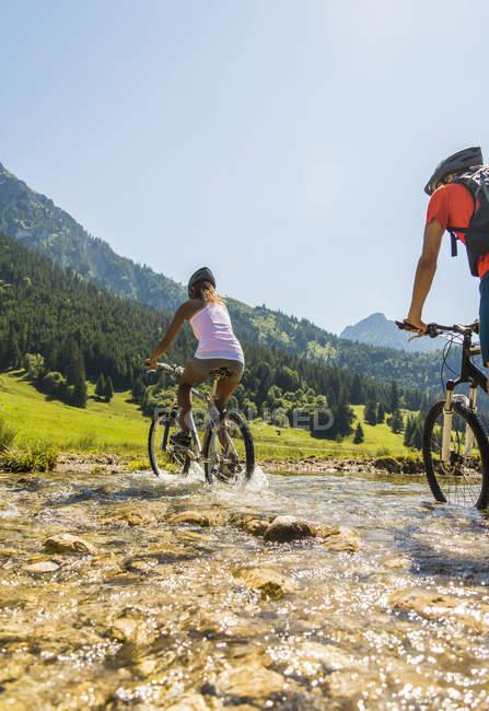 Austria, Tyrol, Tannheim Valley, young couple on mountain bikes crossing brook — Stock Photo