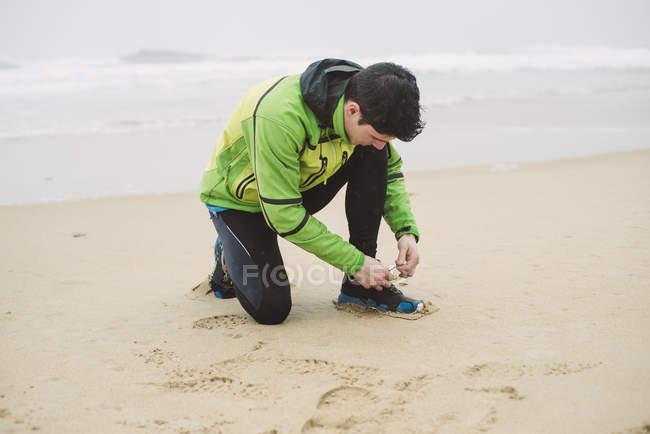 Молода людина, прив'язавши його взуття на пляжі на чорний день — стокове фото