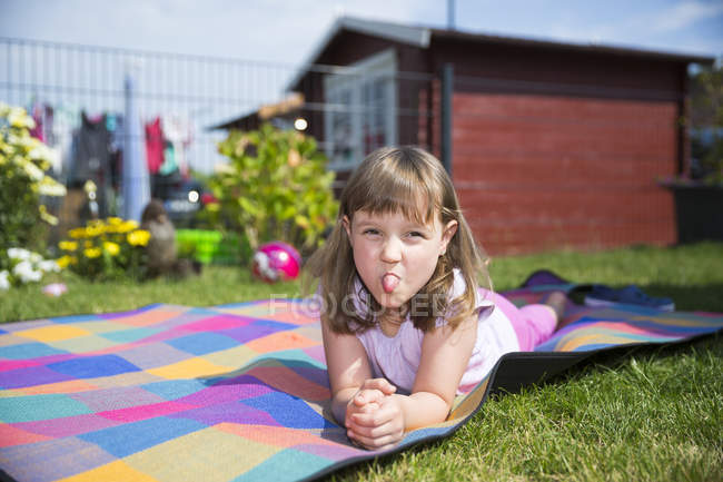 Portrait of little girl lying on a blanket sticking out tongue — Stock Photo