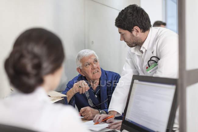 Krankenschwester und Arzt, die Beratung der Patienten an der Rezeption der Klinik — Stockfoto