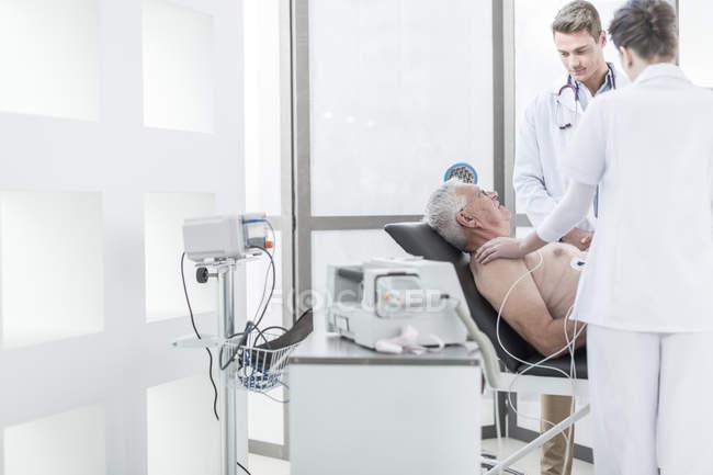 Arzt und Krankenschwester mit Patienten auf Keilrahmen — Stockfoto