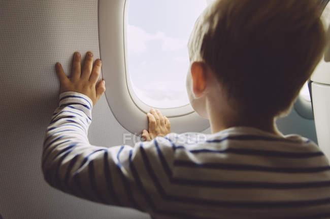 Niño mirando por la ventana mientras vuela en un avión - foto de stock