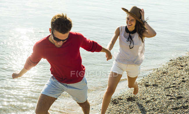 Young couple running hand in hand by the riverside — Stock Photo