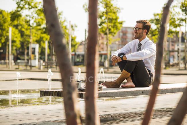 Junger Geschäftsmann sitzt im Schneidersitz auf Bank — Stockfoto