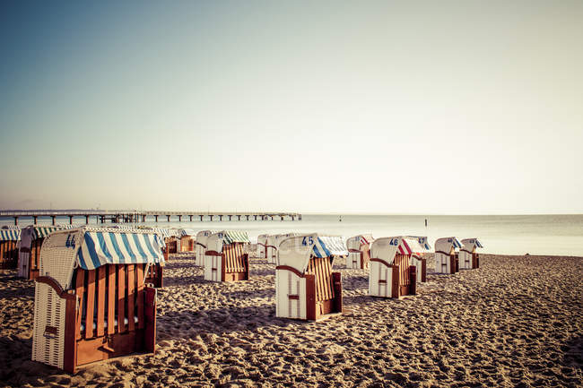 Deutschland, Niendorf, Blick zum Timmendorfer Strand mit Kapuzen Strandkörbe bei Sonnenaufgang — Stockfoto