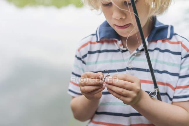 Крупным планом Мальчик готовит удочку рядом с озером — стоковое фото