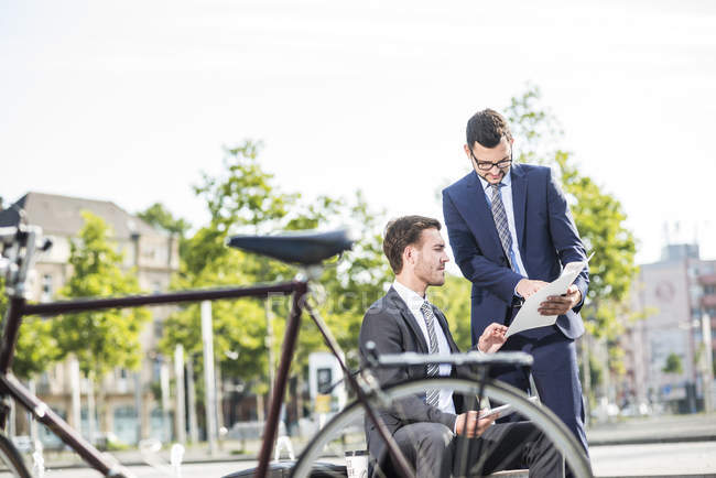 Two young businessmen discussing files outdoor — Stock Photo