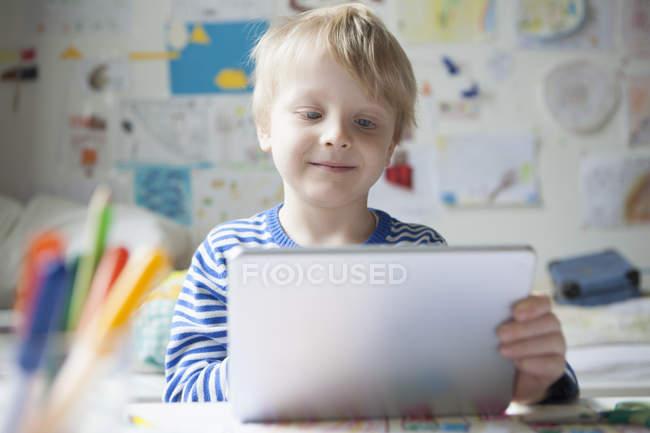 Retrato de menino sorridente usando tablet digital — Fotografia de Stock