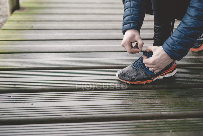Jogger tying lace of sneaker on wooden floor — Stock Photo