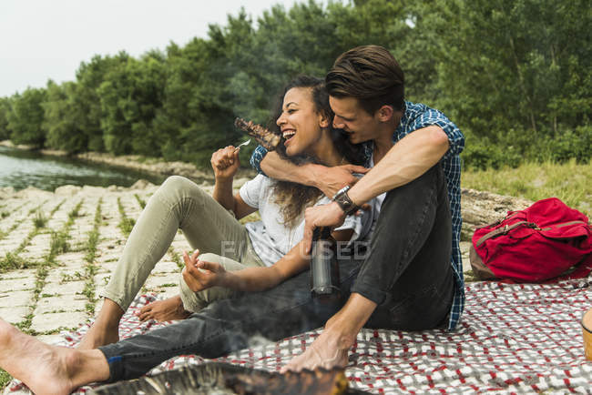 Happy young couple having a barbecue by the riverside — Stock Photo