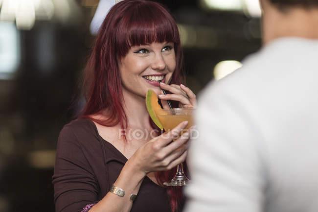 Porträt der lächelnde junge Frau mit Cocktailglas flirten mit jungen Mann — Stockfoto