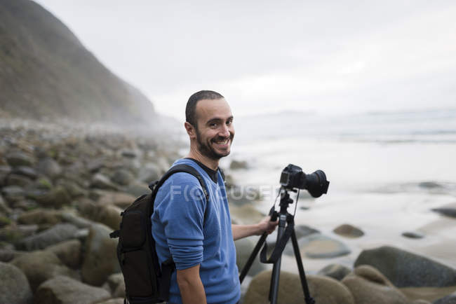 Spain, Valdovino, portrait of smiling photographer on the beach with tripod and camera — Stock Photo