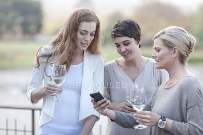 Three women with glasses and smartphone on terrace of a restaurant — Stock Photo