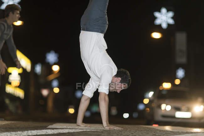 Jovem caminhando sobre as mãos no pavimento à noite — Fotografia de Stock