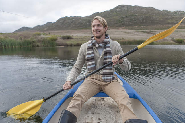 Portrait of happy young man paddling on a lake — Stock Photo