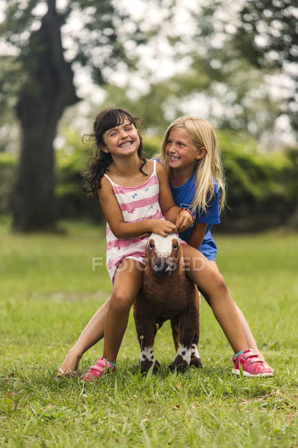 Two laughing girls sitting together on toy horse — Stock Photo