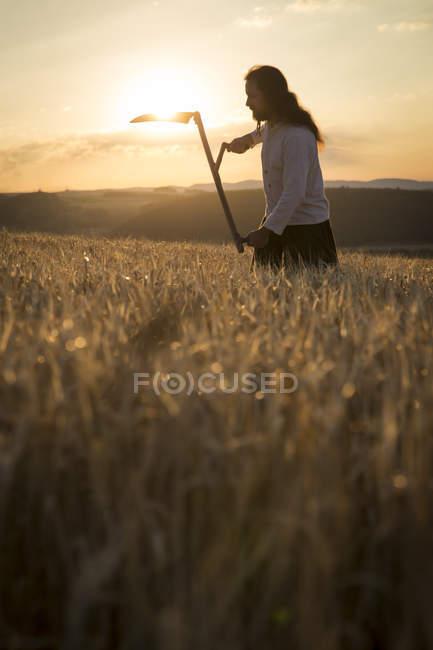Bio-Bauer mit Sense im Gerstenfeld bei Sonnenaufgang — Stockfoto