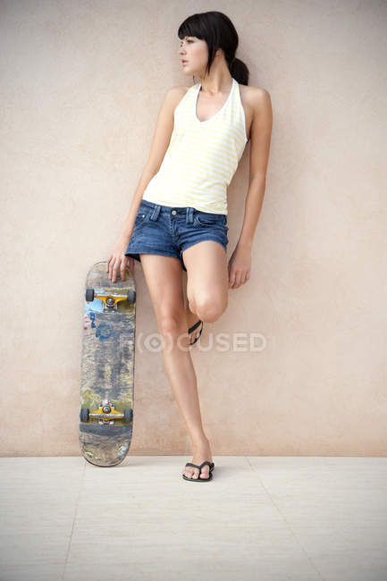 Young woman with longboard leaning against wall — Stock Photo