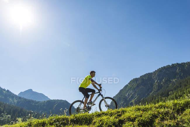 Austria, Tirolo, Valle di Tannheim, giovane in mountain bike nel paesaggio alpino — Foto stock