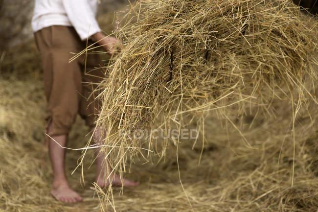 Paysan travaillant dans une grange à foin — Photo de stock