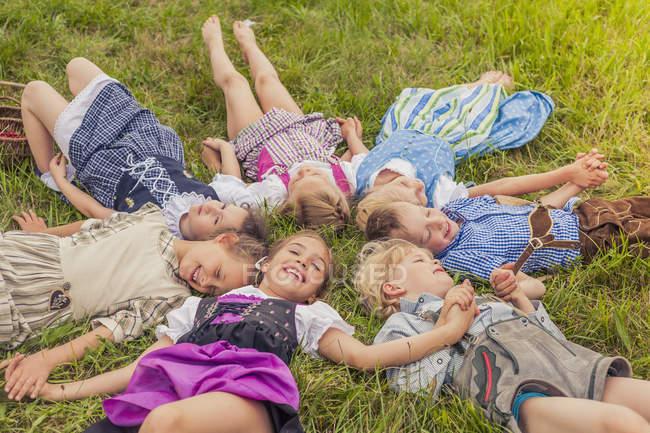 Группа детей в традиционной одежде, лежащих на лугу по кругу — стоковое фото