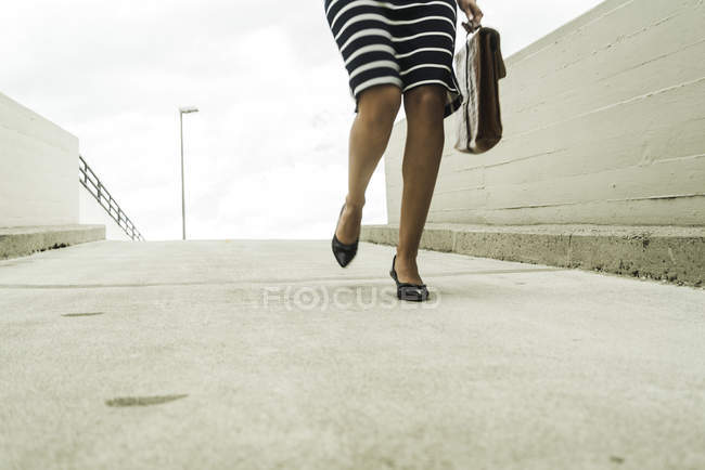 Young businesswoman walking on parking deck — Stock Photo