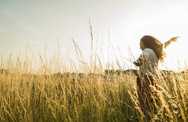 Young woman standing in field with tall grass — Stock Photo