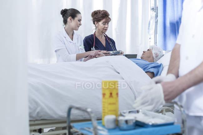 Ärzte stehen im Krankenhaus am Krankenbett — Stockfoto