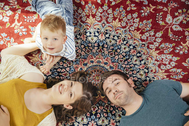 Portrait de parents et petit garçon allongé sur un tapis persan à la maison — Photo de stock