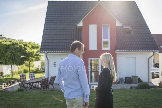 Estate agent and customer standing in front of one-family house — Stock Photo