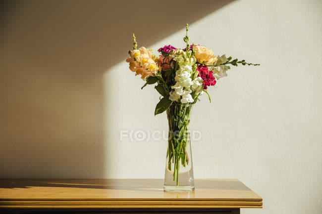 Small bouquet of summer flowers on old wooden sideboard — Stock Photo