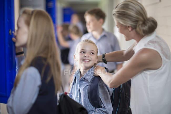 Professor, ajudando o estudante com a mochila no corredor — Fotografia de Stock