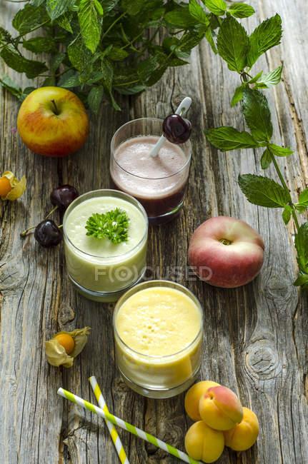 Batido de cereza, batido de melocotón albaricoque, batido de menta perejil y frutas - foto de stock