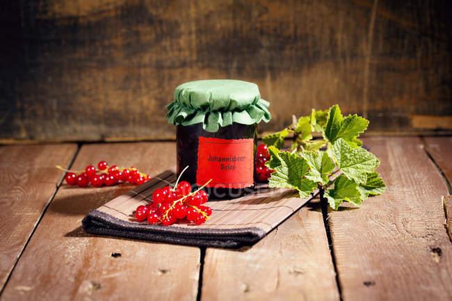 Крупным планом зрения банку домашнего смородины со свежими ягодами и листьями — стоковое фото