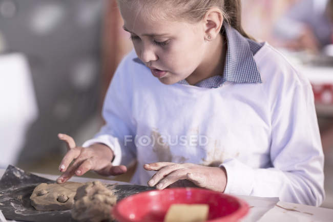 girl working on modeling clay in art class at school stock photo