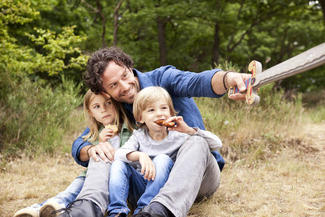 Father with two children in the nature holding wooden sword — Stock Photo