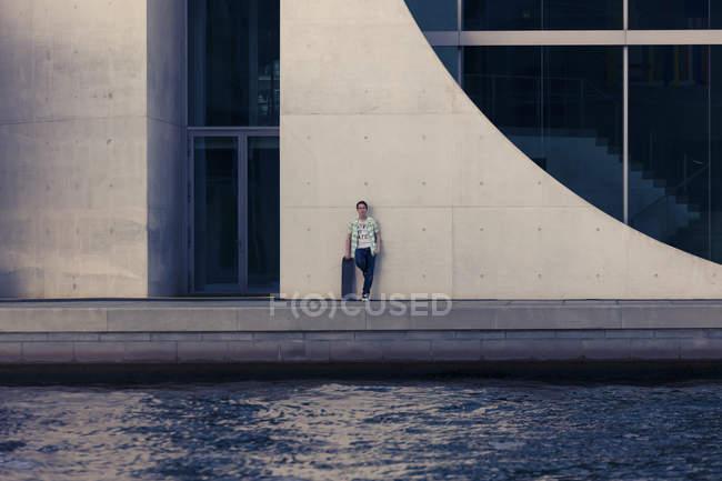 Adolescente de Alemania, Berlín, con patín apoyado por fachada - foto de stock