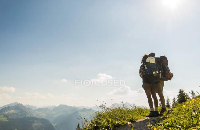 Австрія, Тіроль, Tannheimer-Таль, молода пара, стоячи на слід гори, дивлячись на вид — стокове фото